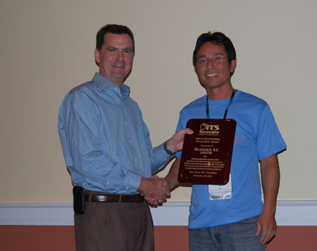 Tom Sever (L) present the Volunteer of the Year Award to Xuewen Le, HNTB