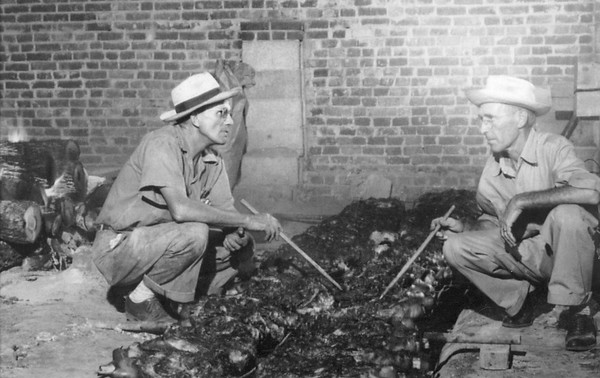 Troy Loftis on the left tends the Fayette, Alabama Fourth of July barbecue in 1953. His assistant is unidentified. Note the fire on the far left where hickory logs are being reduced to charcoal.