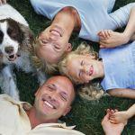 Mama, tata, copilul si un catel (al lor animal de companie), stand culcati pe iarba, in cerc