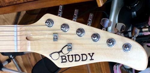 Buddy Holly's distinct black frames adorn the headstock.