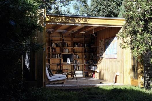 25551126 180611 Hackney Shed ที่ทำงานในสวน ตกแต่งด้วยชั้นหนังสือ ผนังเปิดโล่งรับสีเขียว กับหลังคาที่มองเห็นท้องฟ้า