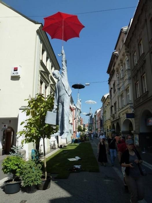 ประติมากรรม รูปปั้นคอนกรีต คนถือร่มลอยเหนือถนน สะท้อนวิกฤตเศรษฐกิจที่ Czech Street 13 -