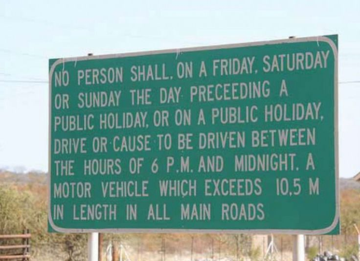 "Road sign that says ""No person shall, on a Friday, Saturday or Sunday the day preceding a public holiday, or on a public holiday, drive or cause to be driven between the hours of 6 P.M. and midnight. A motor vehicle which exceeds 10.5 m in length in all main roads."""
