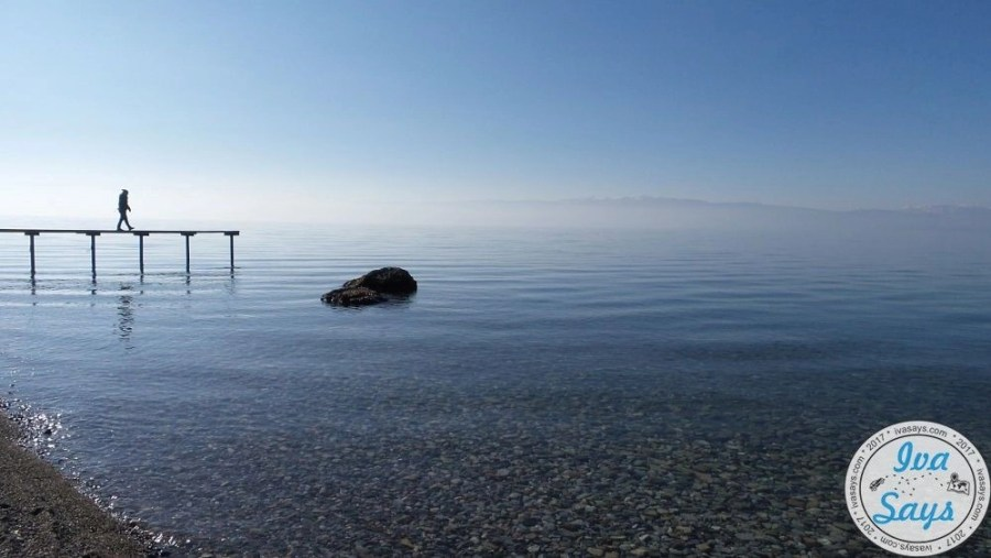 Wooden port in Lake Ohrid with a woman walking on it. Misty and cold atmosphere with mountains and snow in the background, but a crystal clear water.