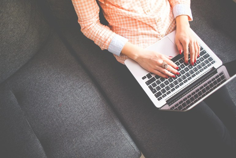 Lady sitting on couch typing on laptop feature image for ow To Improve Your Blog Content In 4 Simple Steps