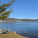 A body of water of Sheppard Lake in Ringwood State Park, NJ with snow on mountains over the horizon.