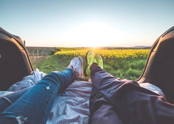 A couple laying in the back of a car looking into the horizon and field of flowers.