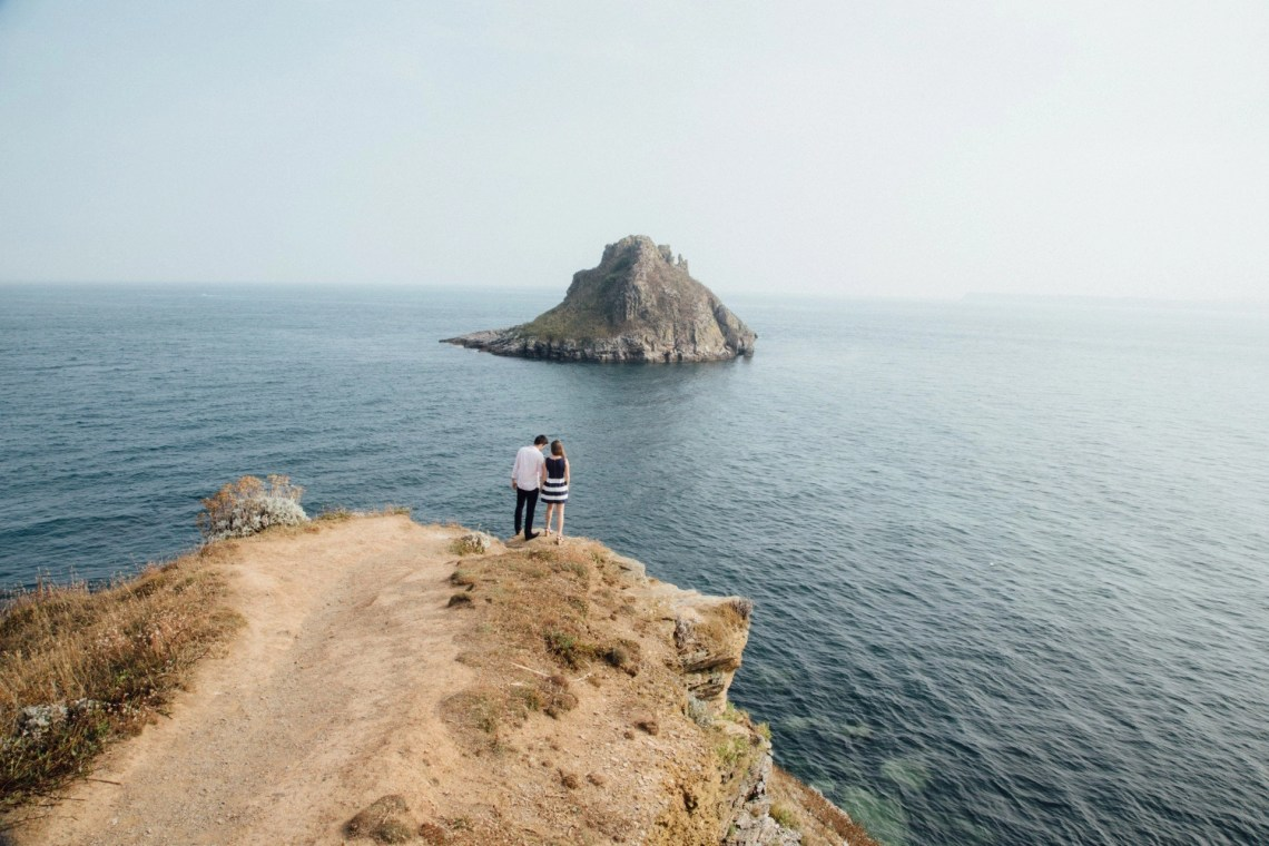 A couple standing by the edge of a cliff overlooking a body of water with a small rock island in the middle of the water enjoying a couple's getaway.