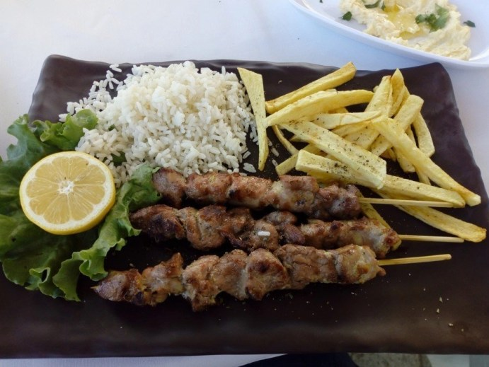 Greek dish of Souvlaki, rice, and french fries on a black plate.