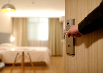 A man's hand on a door handle to a hotel's room with the door partially open to show a view to the room. The bed and a small three-legged table are exposed with the door opened. Cheeky Tips that will Help You To Score a Cheap Hotel Room.