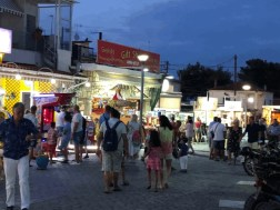 Large group of tourists and locals walking on a street in Chaniotis, Greece.