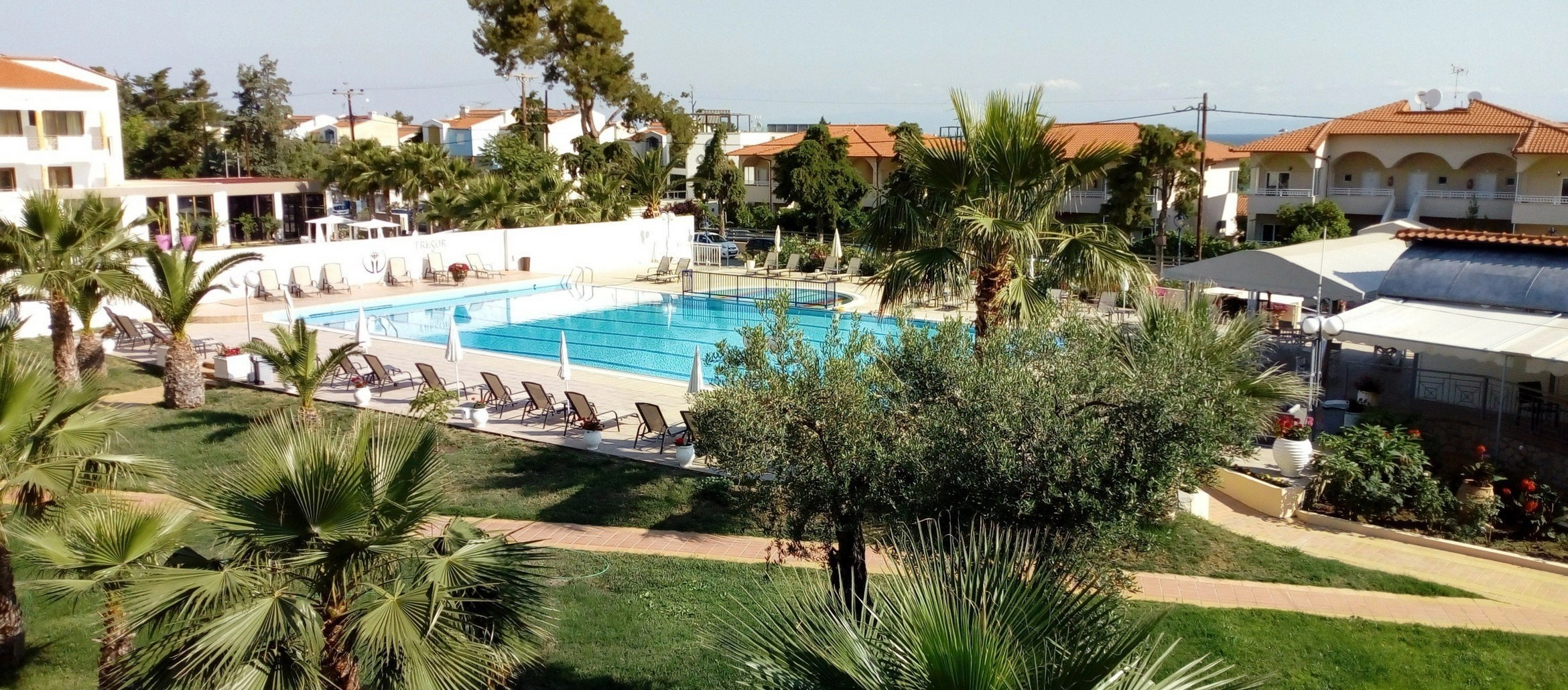 Large swimming pool in the backyard of the Tresor Sousouras Hotel ATTACHMENT DETAILS Tresor-Sousuras-Hotel-Greece-Cover.jpg June 24, 2018 794 KB 2340 × 1030 Edit Image Delete Permanently URL https://www.ivasays.com/wp-content/uploads/2018/06/Tresor-Sousuras-Hotel-Greece-Cover.jpg Title Tresor Sousuras Hotel in Chaniotis, Greece with palm trees around it.