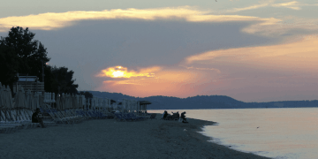 Sunset over the beach in Chaniotis, Greece. The sun going down with clouds around it to produce nice orange, red colors over the horizon and sea in Chaniotis, Greece.