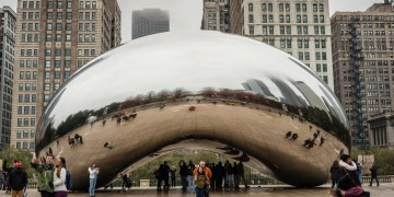 Visitors and tourists in Chicago taking pictures of the The Cloud Gate sculpture also known as 'the Metal Bean' in Chicago Illinois with several skyscrapers in the background.