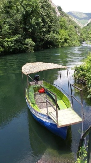 Small boat used for tours to take visitors to cave Vrelo in canyon Matka.