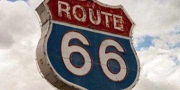 The route 66 sign, commonly associated with a cross country US road trip. White letters of the word route and numbers 66 in white on a blue background.