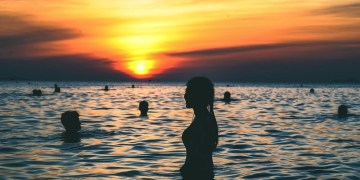 Silhouette of a person standing in a body of water with the sunset going down.