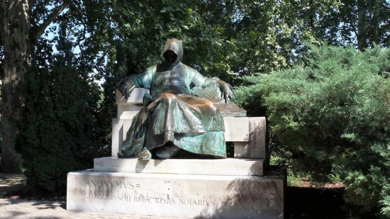 Anonymus Szobor also known as the Anonymous statue. A person covered in robe holding a book and a writing utensil.