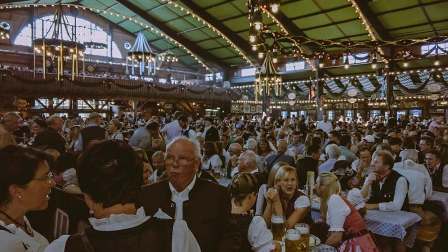 People sitting at tables and walking around in a tent at Oktoberfest.
