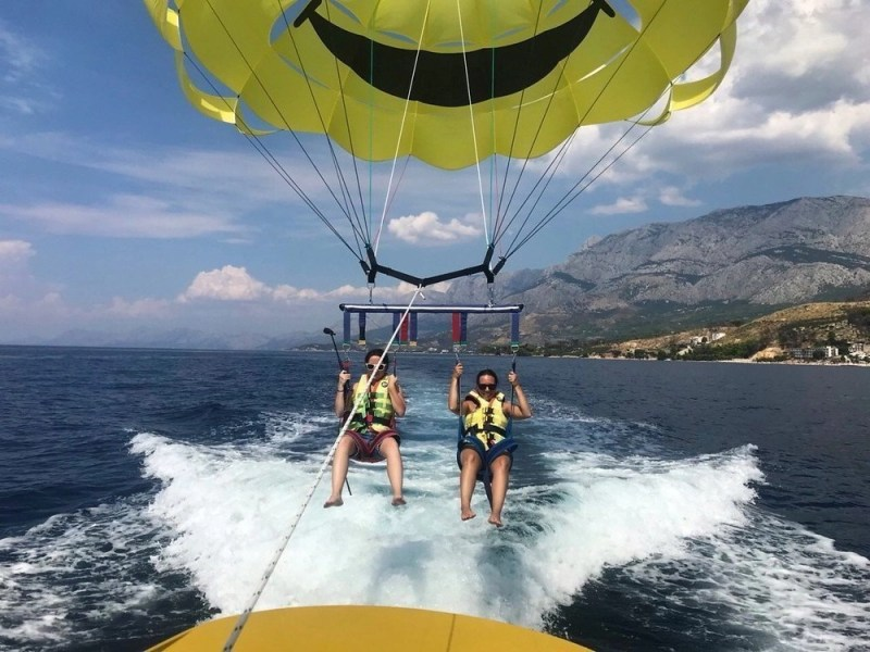 Two people strapped to a parachute for parasailing over the Adriatic Sea in Podgora, Croatia.