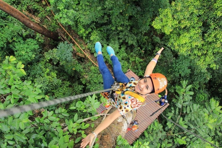Woman tied to zip line gear.