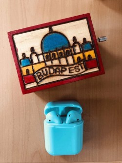 wireless green earpods next to a Budapest wooden music box