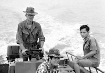 Lieutenant Davis driving boat in Vietnam