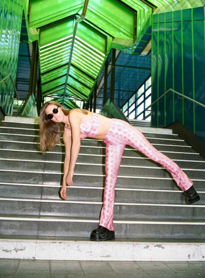 girl with pink neon leggings and crop bending over on staircase