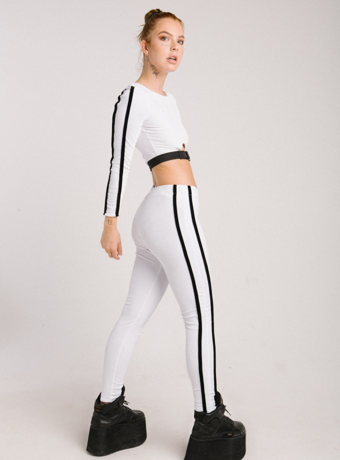 white top with black stripes down the arms and white leggings with black stripes down legs