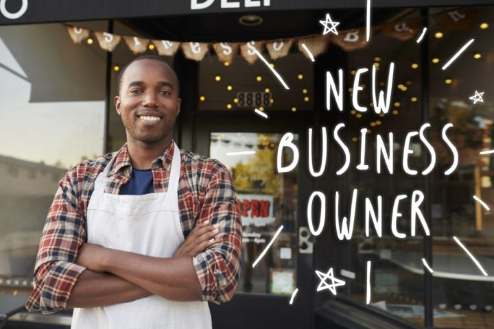 """Man standing outside cafe that says """"new business owner"""""""