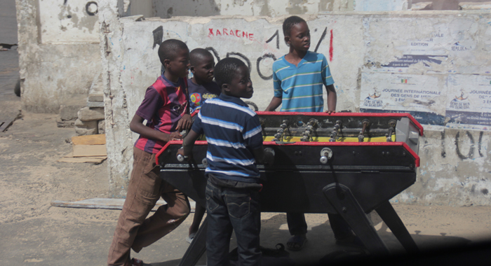 Children play table football at a roadside in Dakar. (IWN photo)