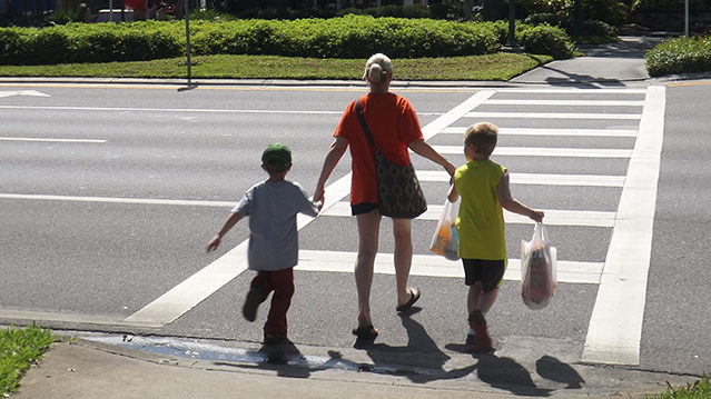 Mother And Children Cross At Crosswalk