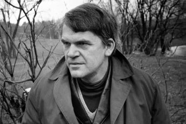 """Czech writer Milan Kundera poses in a garden in Prague 14 October 1973. Novelist born in Brno, Czech Republic, Kundera lectured in Cinematographic studied in Prague until he lost his post after the Russian invasion in 1968. His first novel, Zert (1967, The Joke), was a satire on Czechoslovakian-style Stalinism. In 1975 he fled to Paris, where he has lived ever since, taking French nationality in 1981. He came to prominence in the West with his """"The book of Laughter and Forgetting"""" in 1979, and """"The Unbearable Lightness of Being"""" in 1984 which was filmed in 1987. (Photo credit should read /AFP/Getty Images)"""