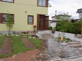 玄関前の茶色の自然石はジャワ鉄平です。