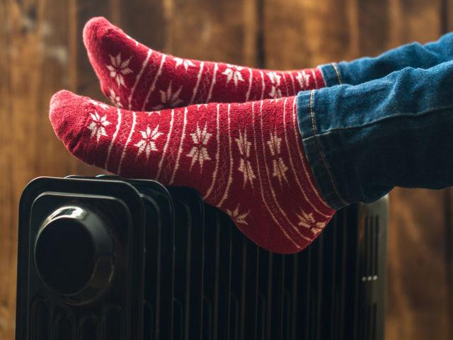 Women's,Feet,In,Christmas,,Warm,,Winter,Socks,On,The,Heater.