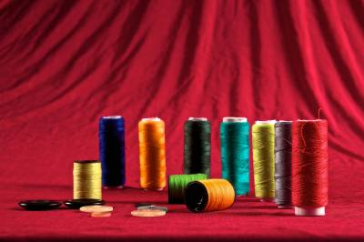 Spools of thread of coloured string against a red background