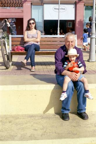 A grandfather with a child and a young woman. Different stages of life.