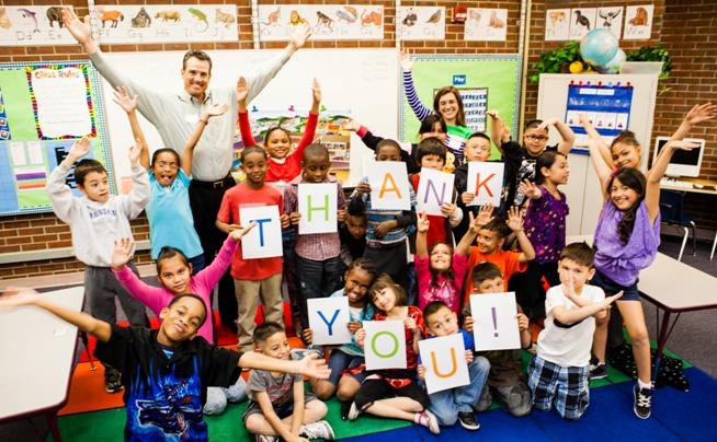 """A group of second grade students in a classroom hold a sign that reads, """"Thank you!"""""""