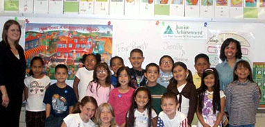 Two adult volunteers posed in a classroom with a large group of elementary school students
