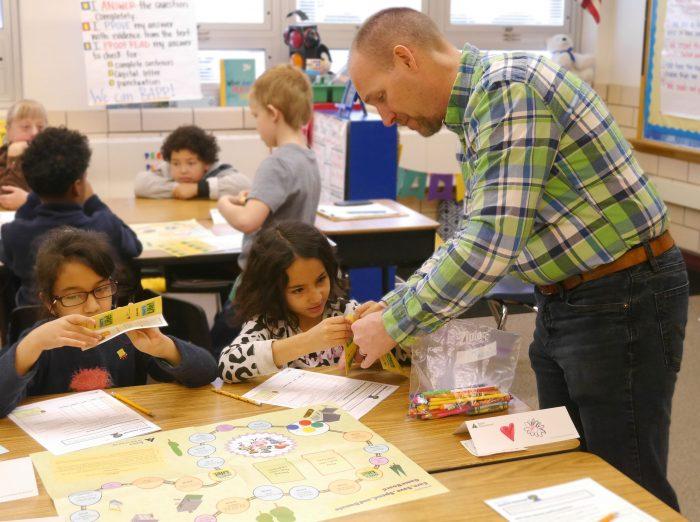 Corporate volunteer working with two girls in Junior Achievement classroom.