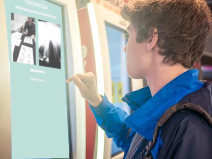 Teen at a touchscreen kiosk taking a digital occupational profile.