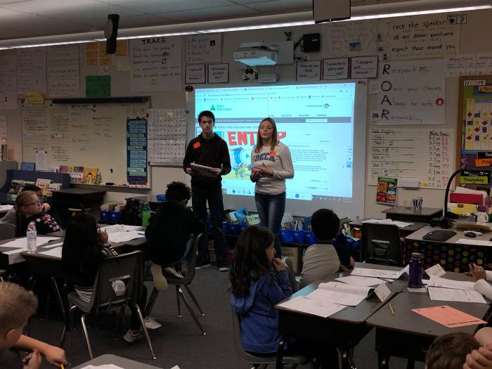 Two high school students in front of elementary school classroom