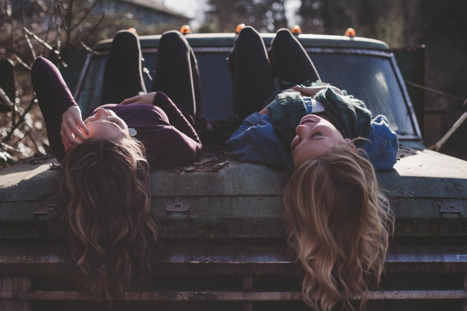 girls laying on car