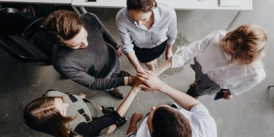 Team Building. The group of colleagues stand in a circle folded their hands together on each other