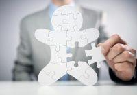 Businessman assembling jigsaw puzzle human team employee