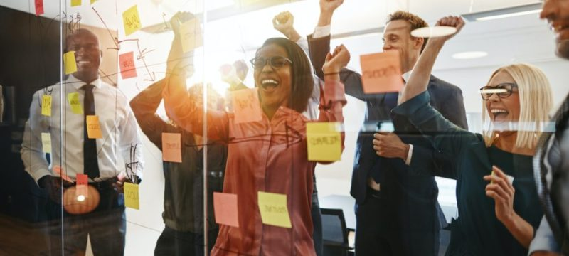 Ecstatic businesspeople celebrating success after an office brainstorming session