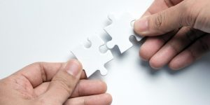 Partnership concept with hands putting puzzle pieces together