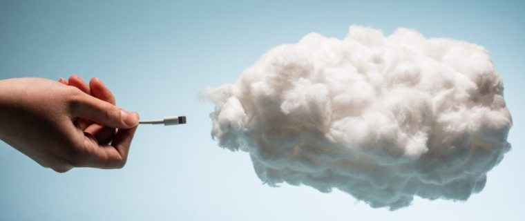 Woman's hand plugging a wire into a white cloud.
