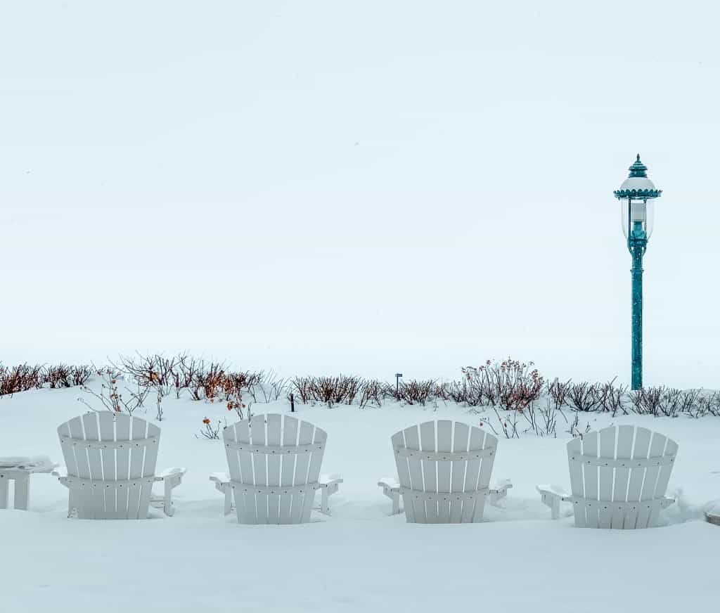 Adirondack chairs stuck in the snow after a particularly heavy snowfall in the Petoskey Wine Region.