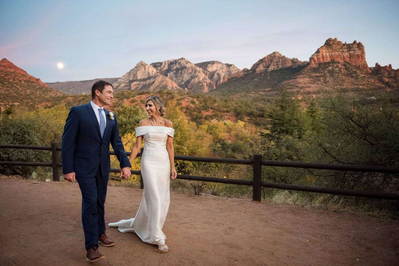 wedding couple walking with moon near red rocks